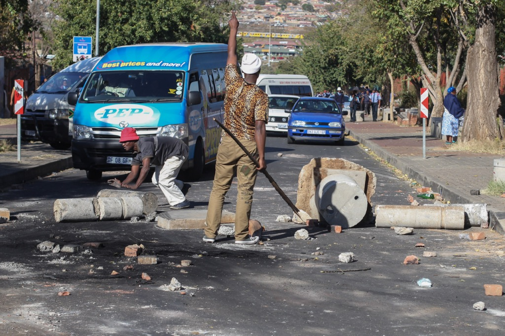 SOUTH AFRICA: Protestors at Orlando West block roads and redirect traffic on Khumalo Street, during an electricity service delivery protest on 06 May 2015. Residents of Orlando West blocked and littered the surrounding areas with rocks, stones and burning tyres during the protest. © JABULILE PEARL HLANZE